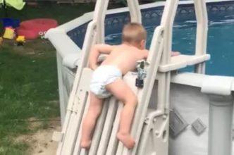 Niño de 2 años trepa por las escaleras de seguridad de una piscina
