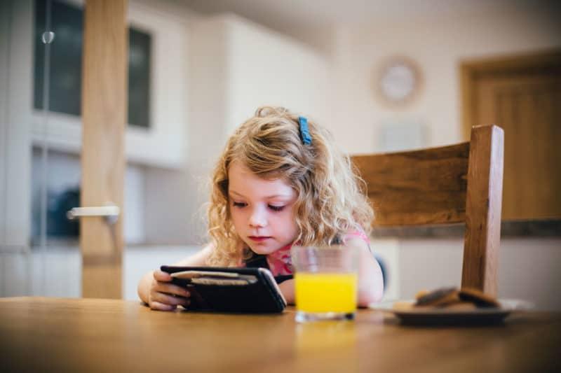 niños comiendo frente móvil